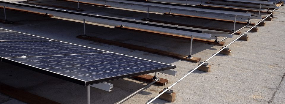 REC solar panels mounted on flat roof using the Snapnrack racking system